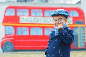 Un enfant devant un bus rouge anglais